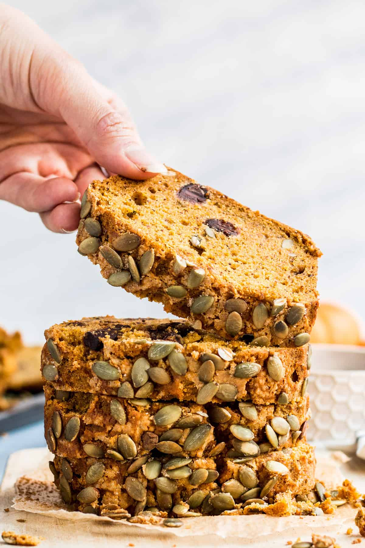 A hand picking up a piece of vegan pumpkin bread from a stack of four pieces of pumpkin bread on parchment paper.