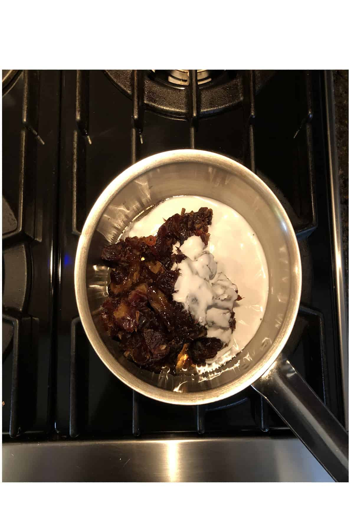Birds eye view of dates, coconut cream, and maple syrup cooking in a pot on top of the stove.