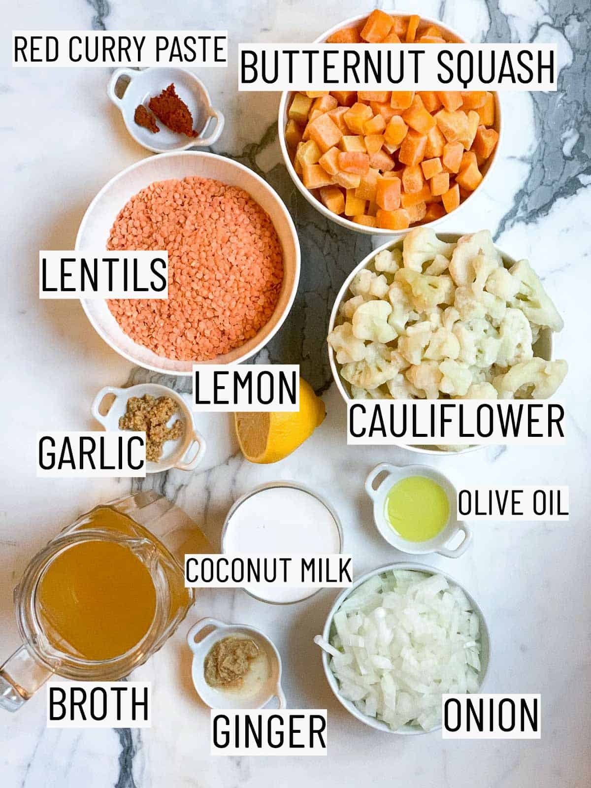 flatlay of ingredients required to make the soup: red curry paste, butternut squash, cauliflower, olive oil, lemon, lentils, garlic, coconut milk, onion, ginger, and broth.