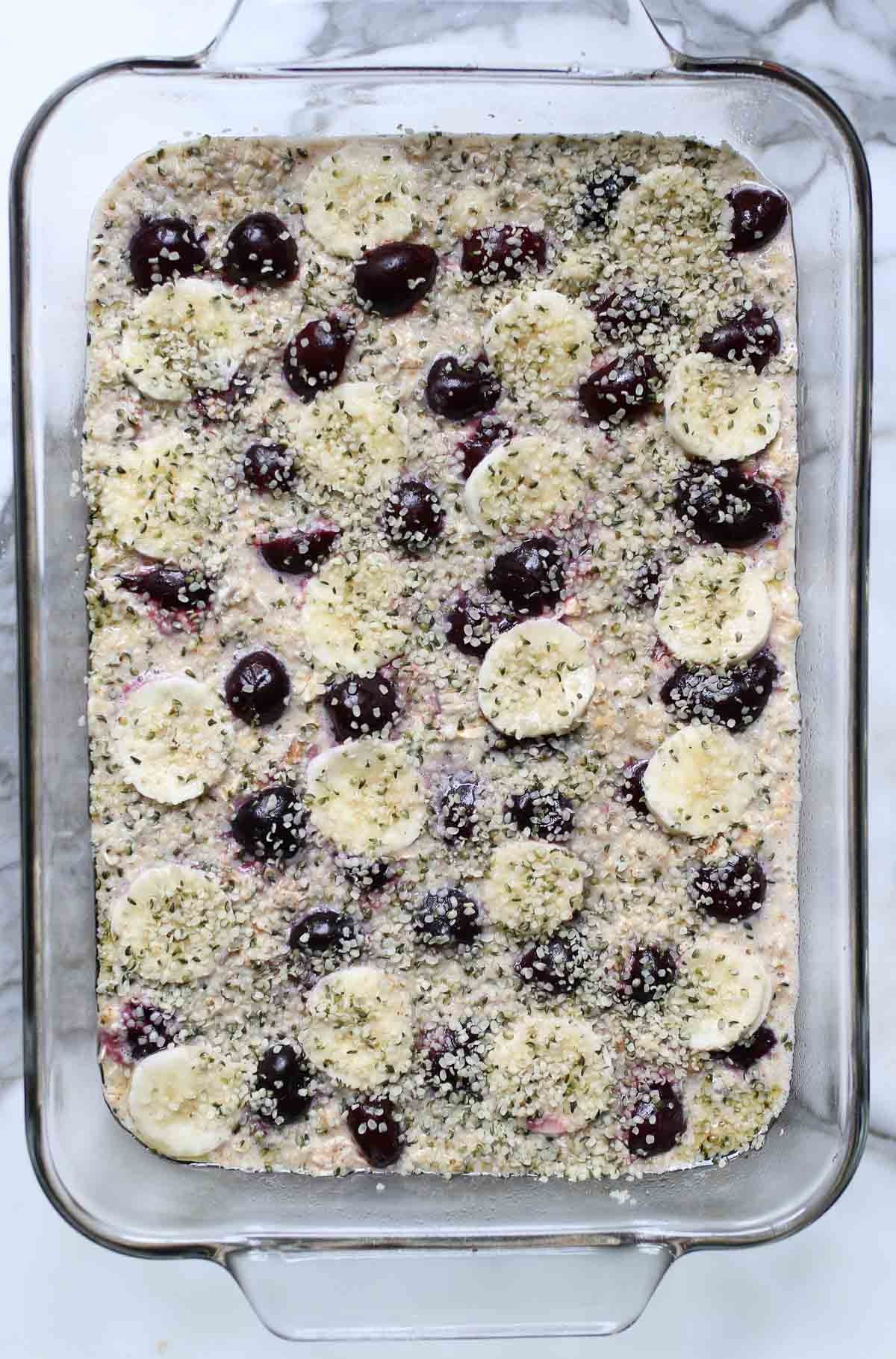 Baked oatmeal mixture added to a baking pan and topped with bananas, cherries, and hemp seeds.