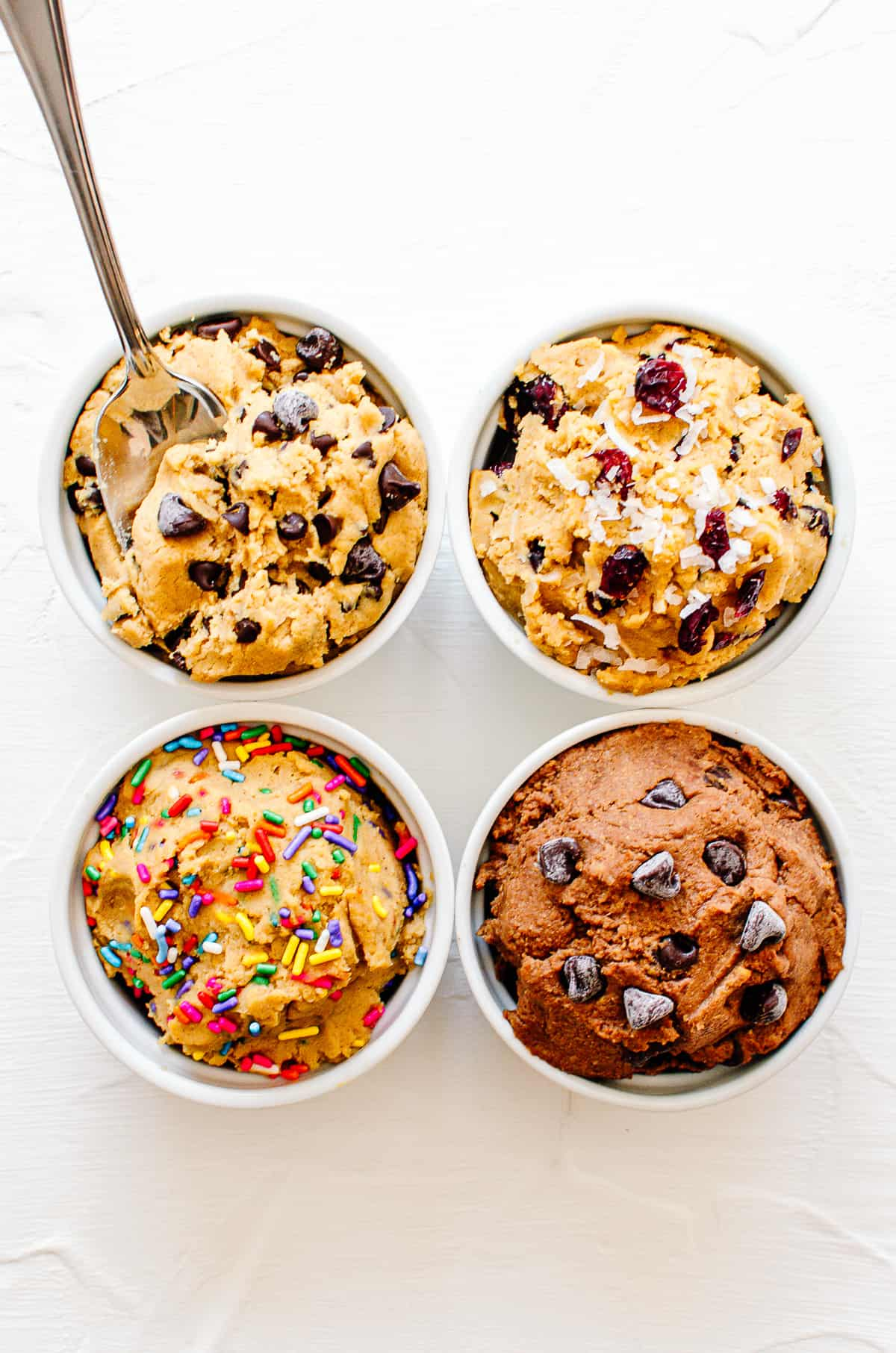 Birds eye view of four chickpea cookie dough flavour combinations in white bowls.