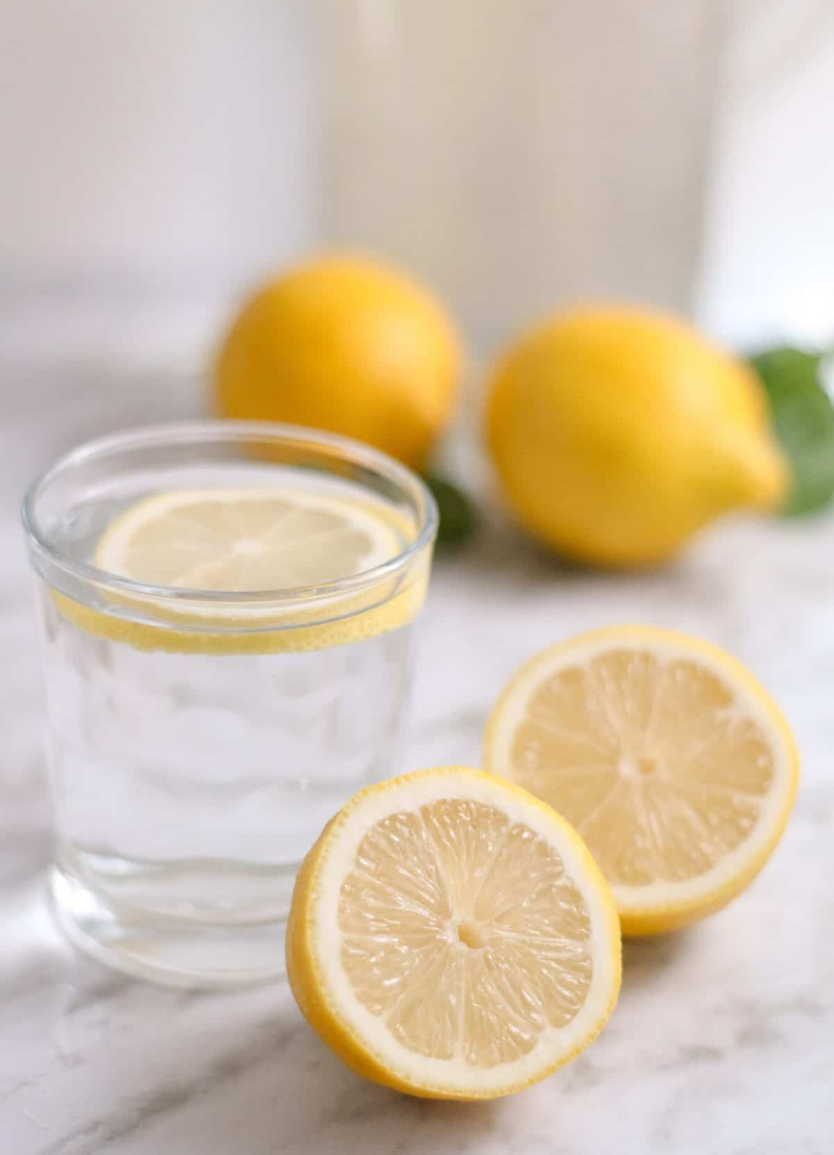 Lemon water with a sliced lemon and two halves of a lemon on the side.
