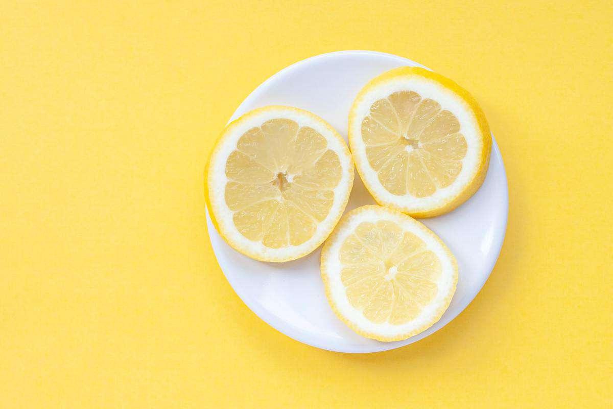 Three lemon slices on a white plate.