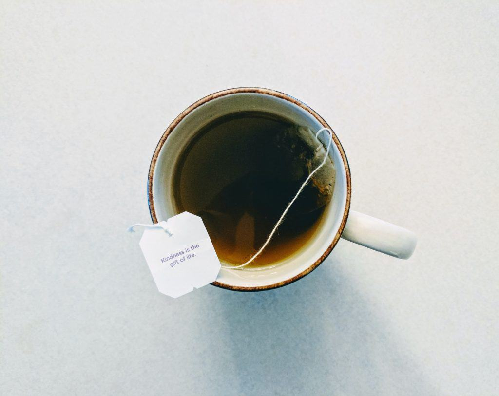 birds eye view of a tea bag steeping in a white mug.