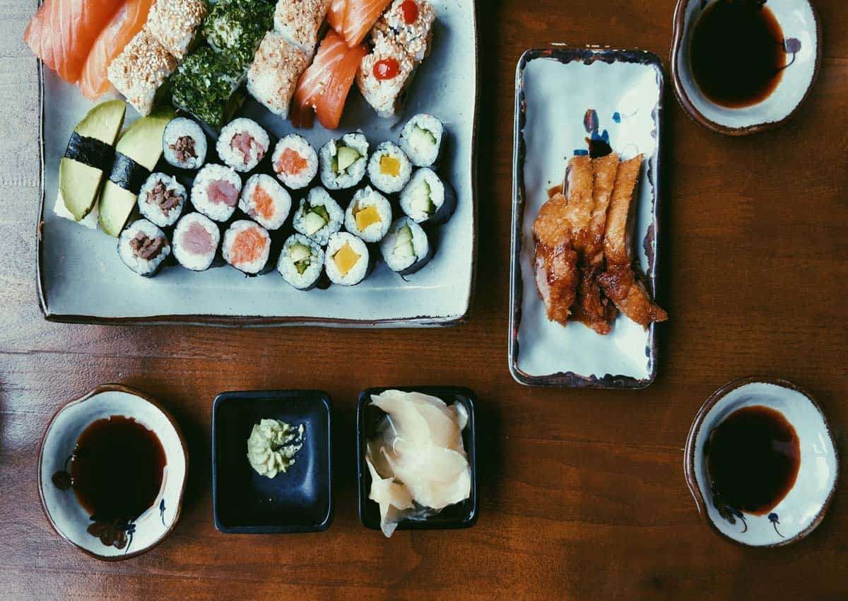 Birds eye view of a sushi platter with ramekins filled with soy sauce.