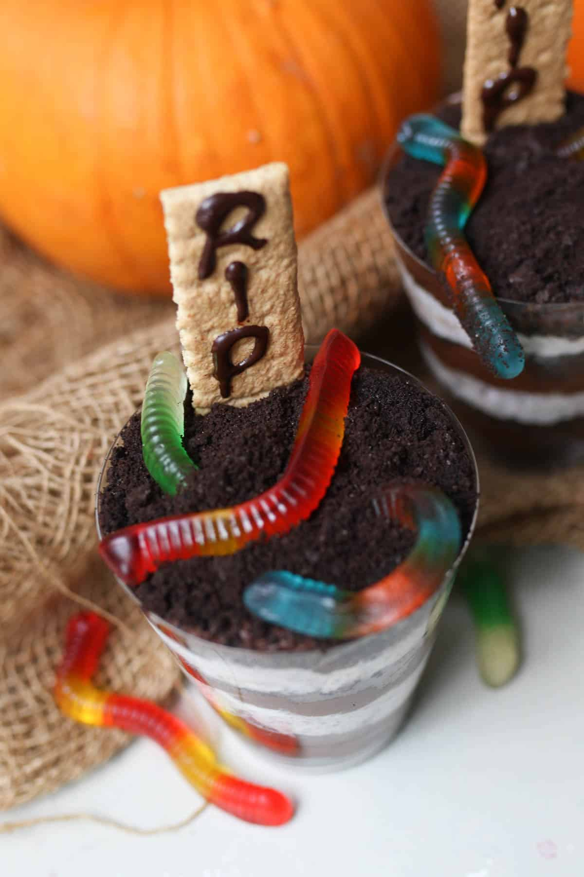 birds eye view of halloween cups with colourful gummy worms on top.