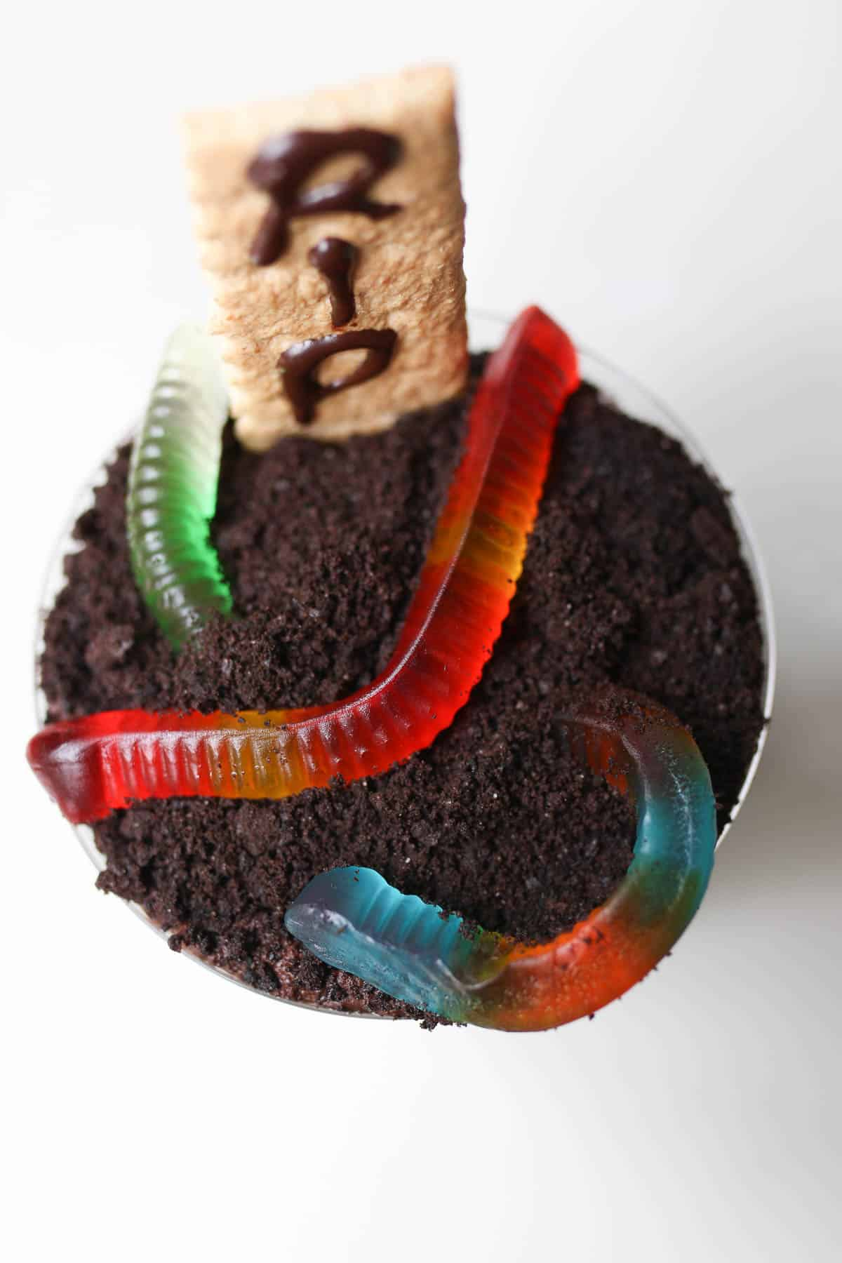 close up of halloween dirt cups with a graham cracker and gummy worms on top.