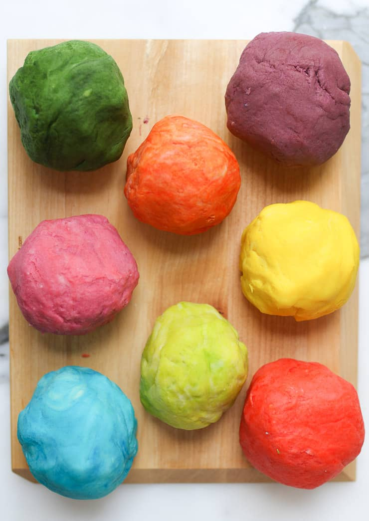 several balls of homemade playdough on a wooden board