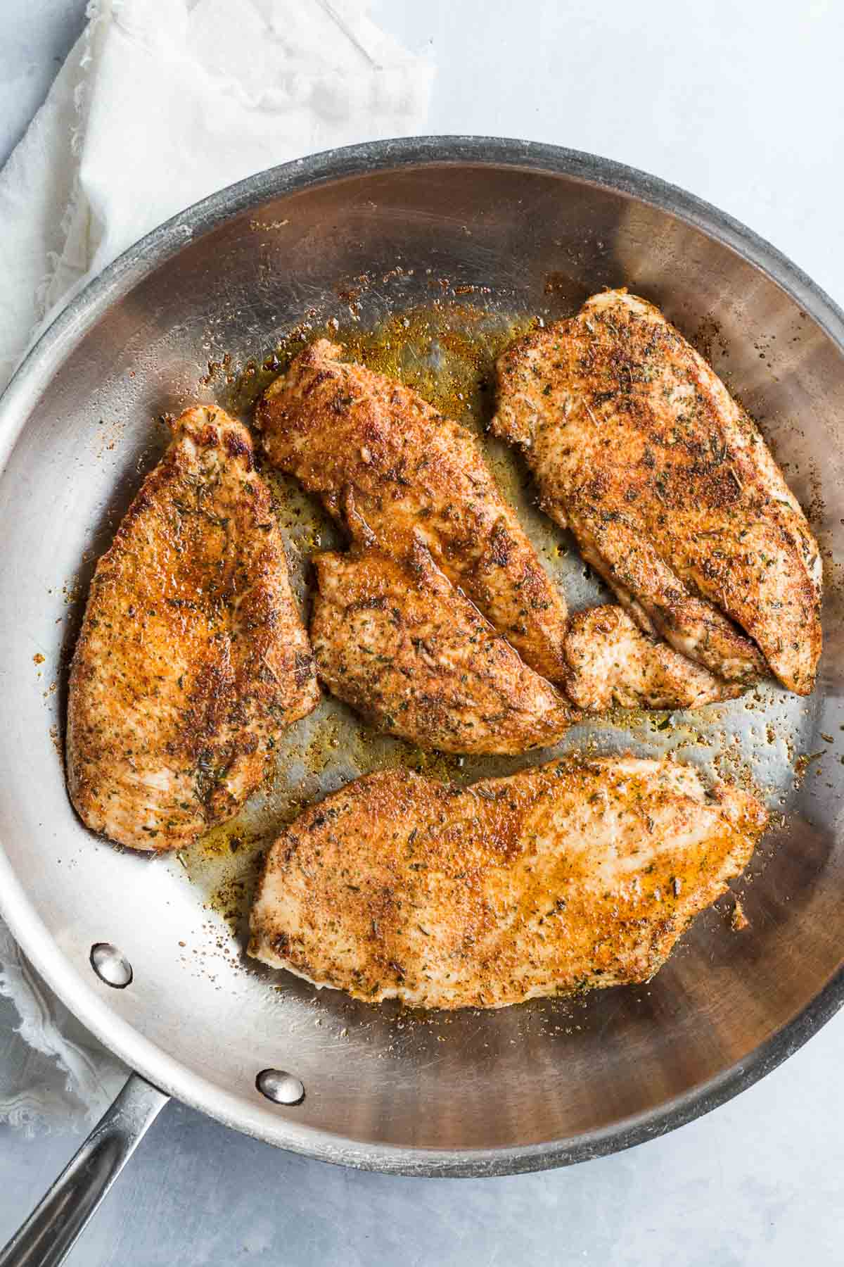 jerk seasoned chicken breasts in a frying pan.