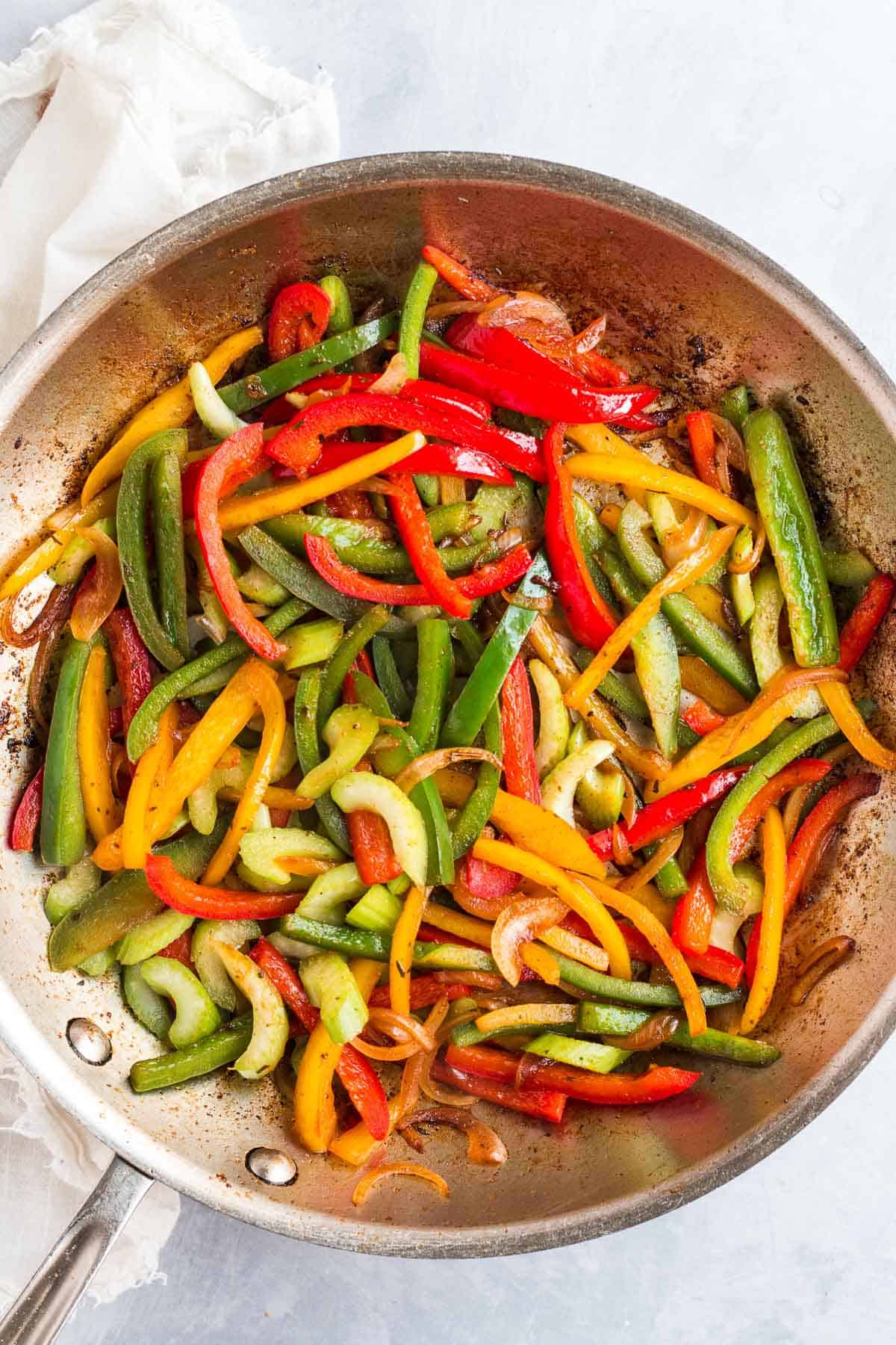 sauteed vegetables in a grey frying pan.