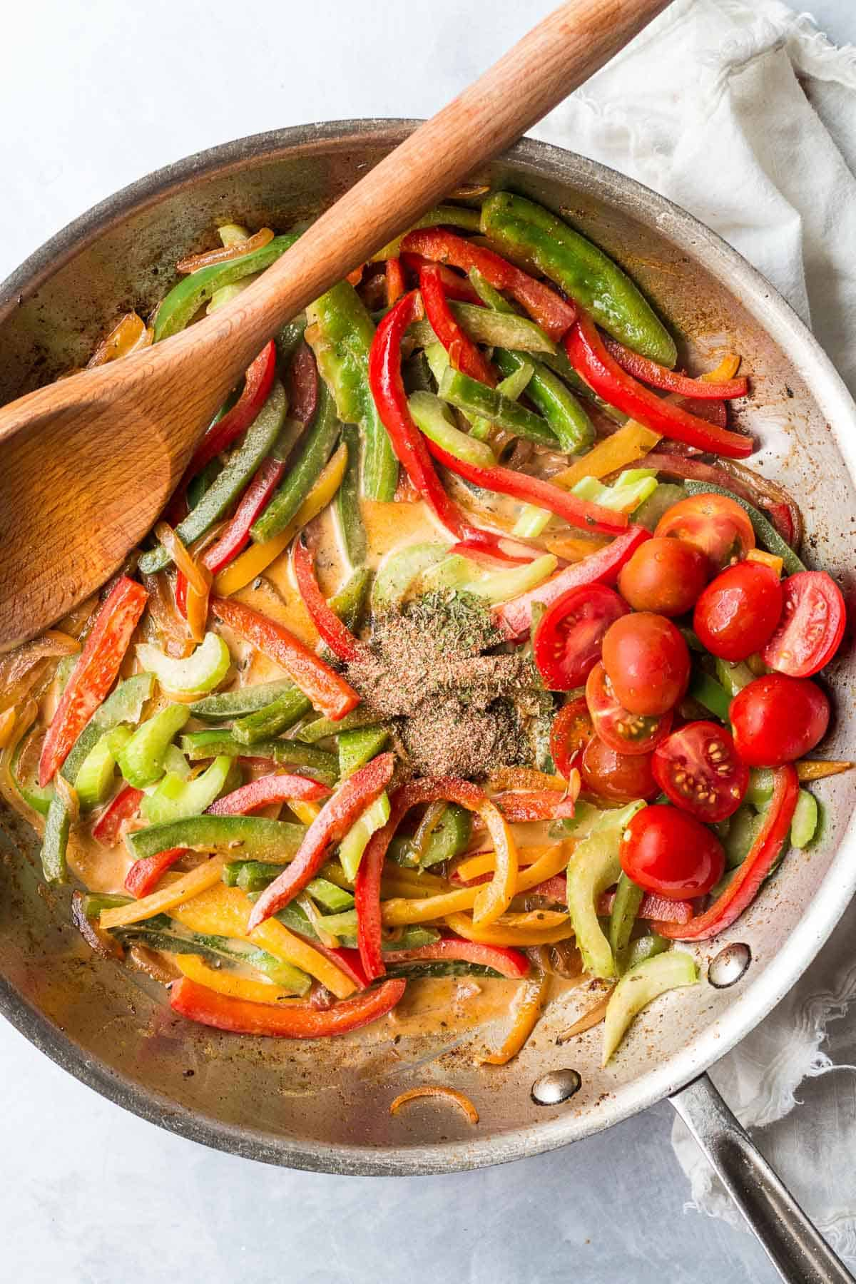 tomatoes and jerk seasoning added to frying pan with bell peppers and celery.