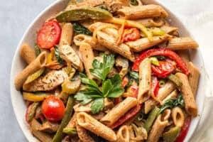 pinterest image of jerk chicken pasta in a white bowl.