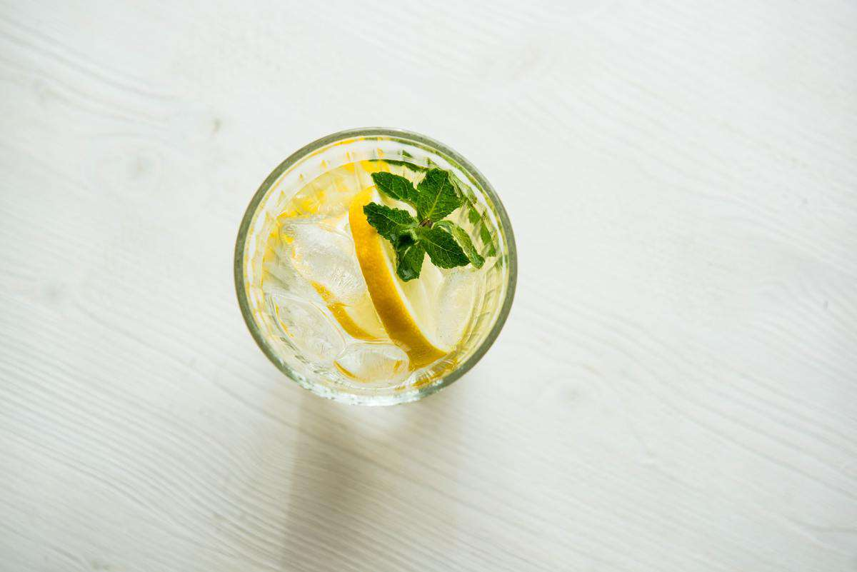 Birds eye view of a glass of lemon water with a mint sprig.