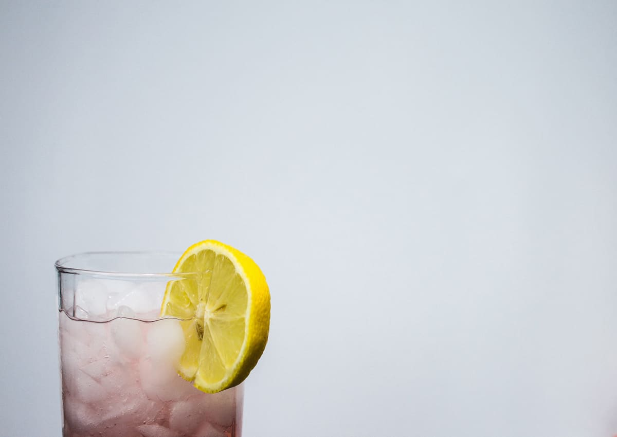 A beverage with ice and a lemon wedge on the rim.