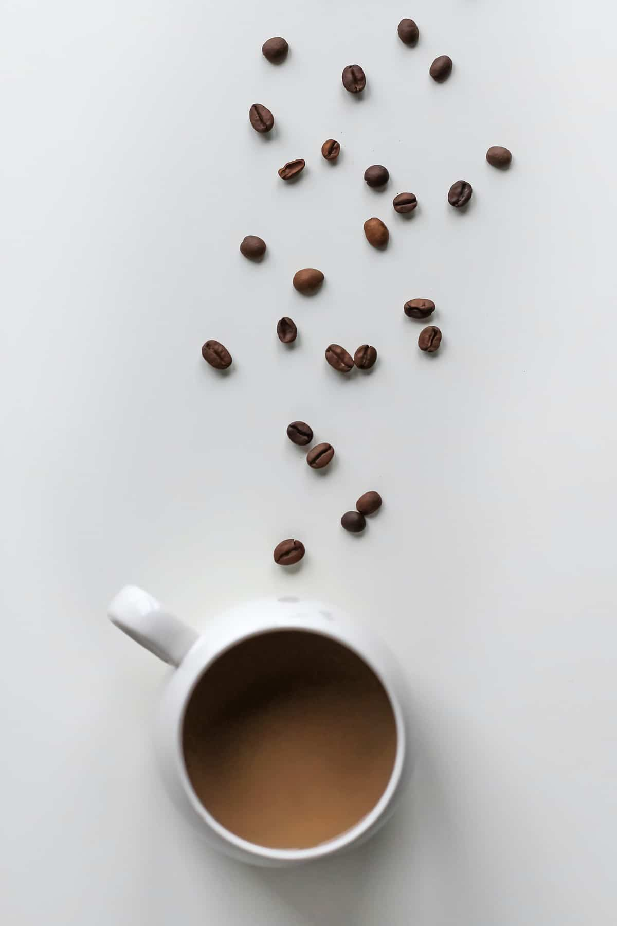 A birds eye view of coffee while intermittent fasting in a white mug with a trail of coffee beans in front of it.