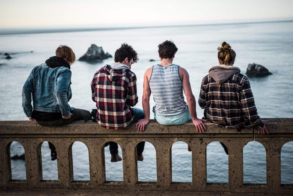 several teens sitting together on a bridge