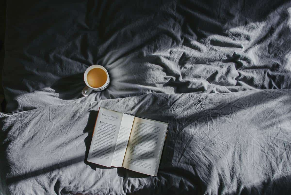 Close up image of a bed with dark grey sheets with an open book laying on a pillow, and a cup of coffee in a mug on top of the bed.