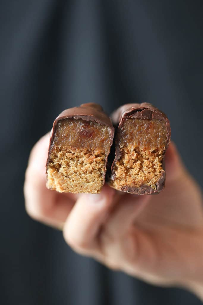 A hand holding up two pieces of a Twix bars.
