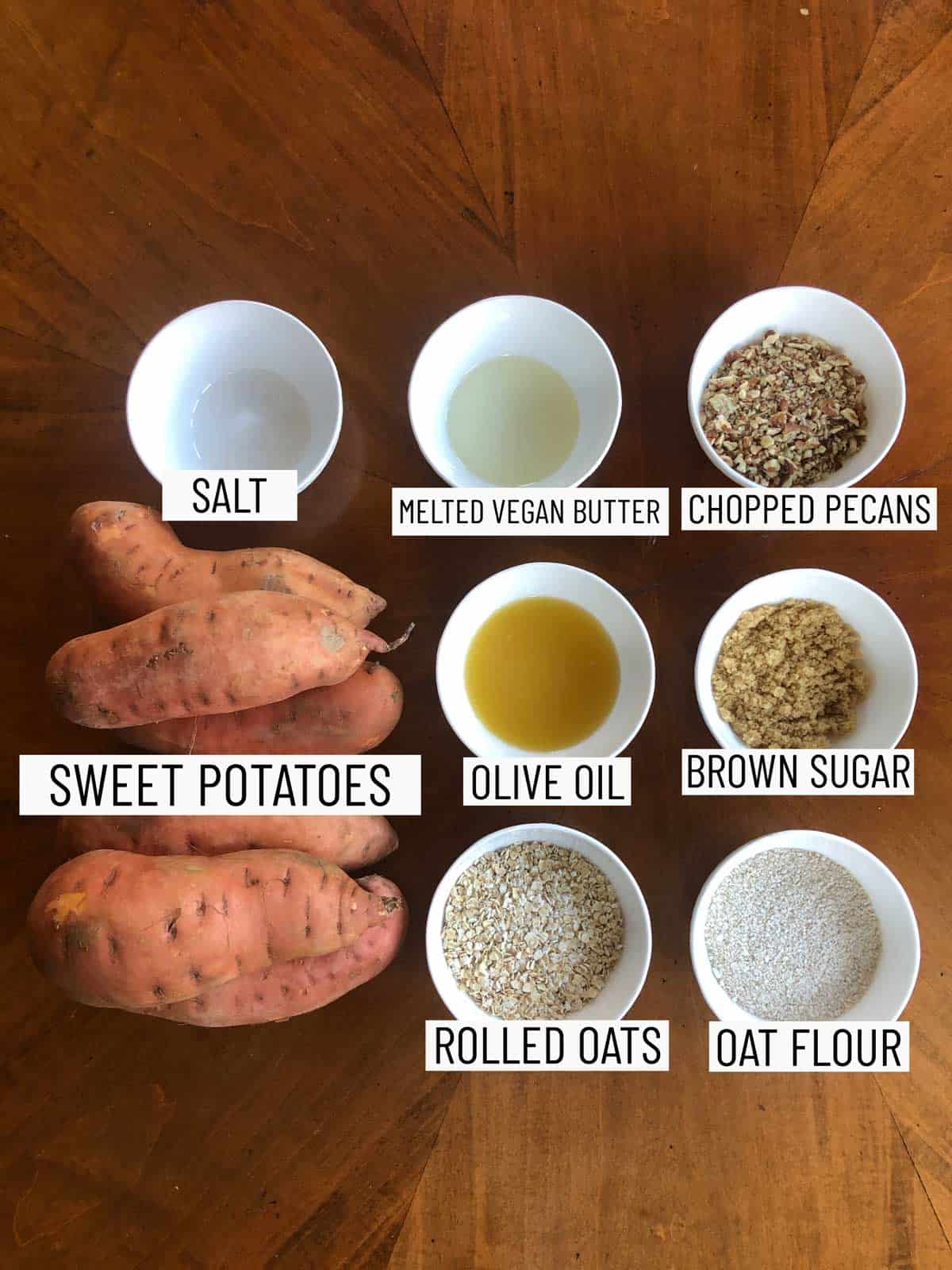 Overhead shot of ingredients to make vegan hasselback sweet potatoes: salt, melted vegan butter, chopped pecans, sweet potatoes, olive oil, brown sugar, rolled oats, and oat flour.