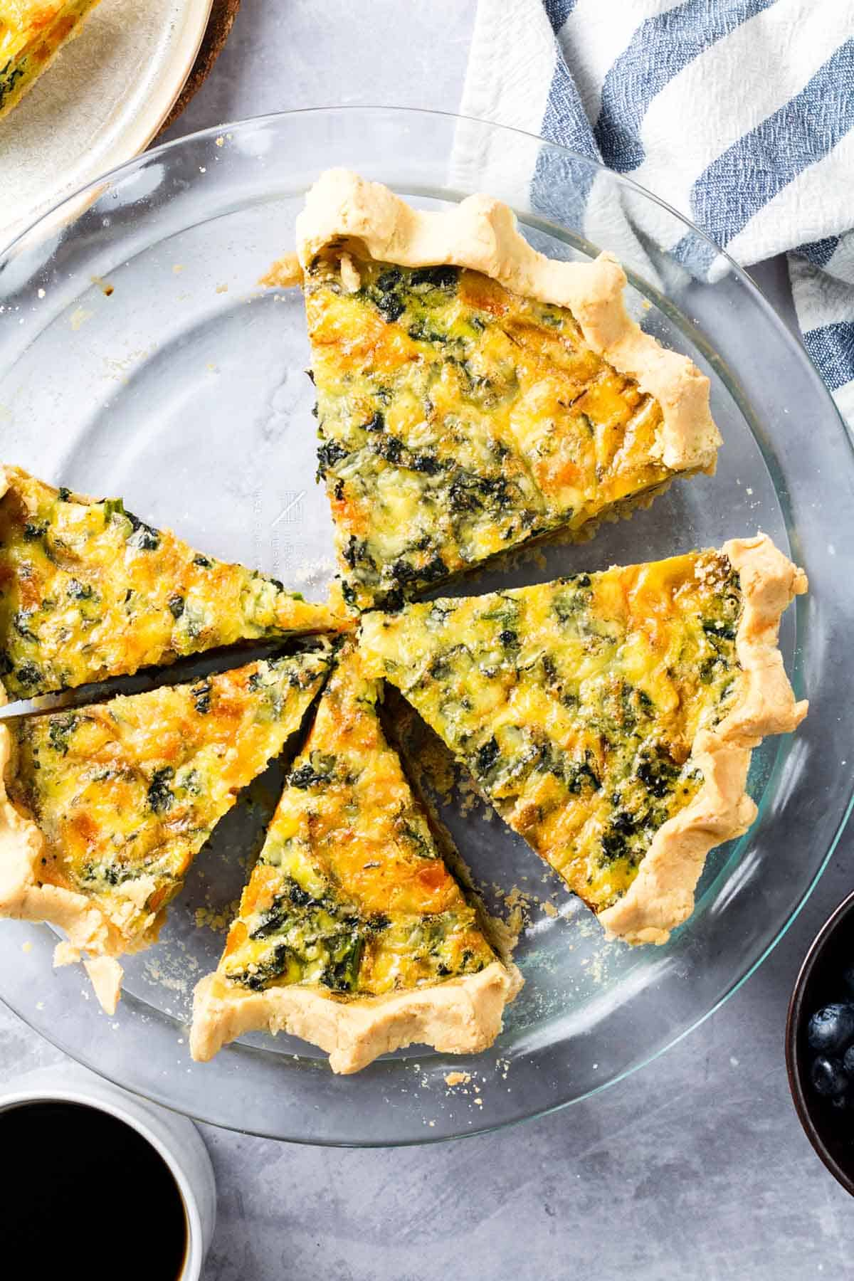 Birds eye view of five slices of gluten free quiche on a clear plate.