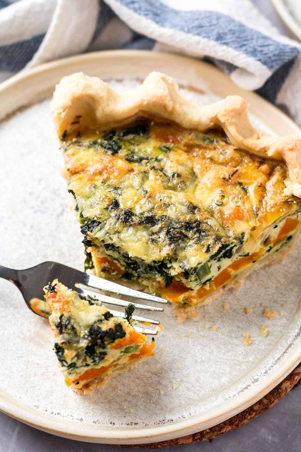 A slice of gluten free quiche on a plate.