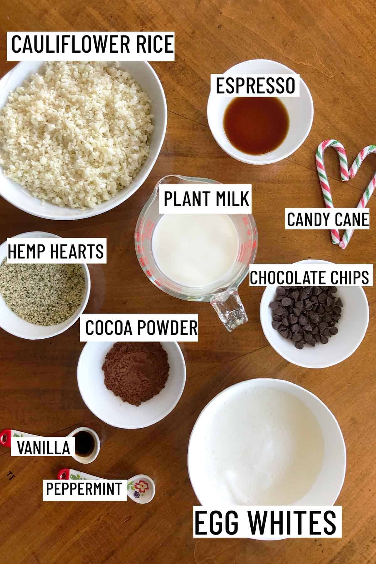 Birds eye view of portioned ingredients to make recipe including espresso, cauliflower rice, hemp hearts, plant milk, chocolate chips, candy canes, cocoa powder, egg whites, vanilla and peppermint extract.