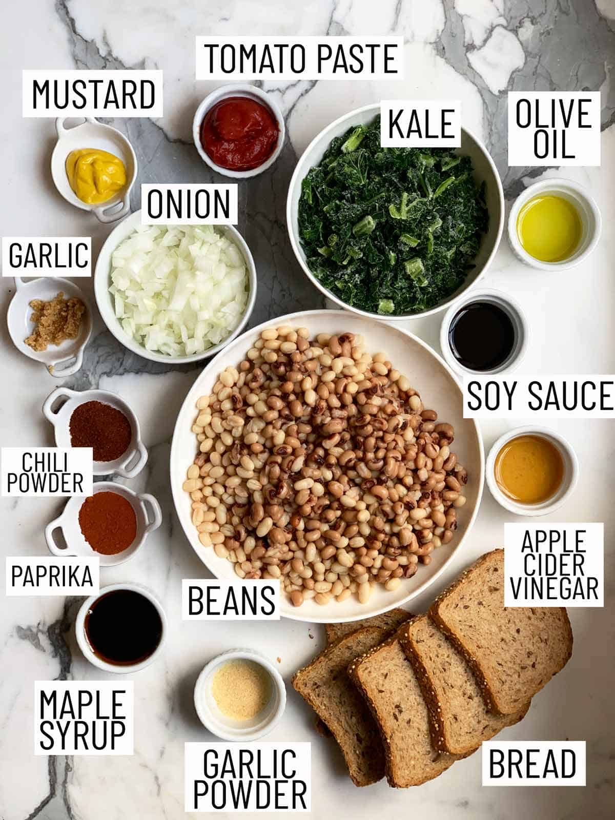 Overhead image of ingredients for beans on toast: mustard, tomato paste, olive oil, minced garlic, onion, chili powder, paprika, maple syrup, garlic powder, bread, apple cider vinegar, soy sauce, beans, and kale.
