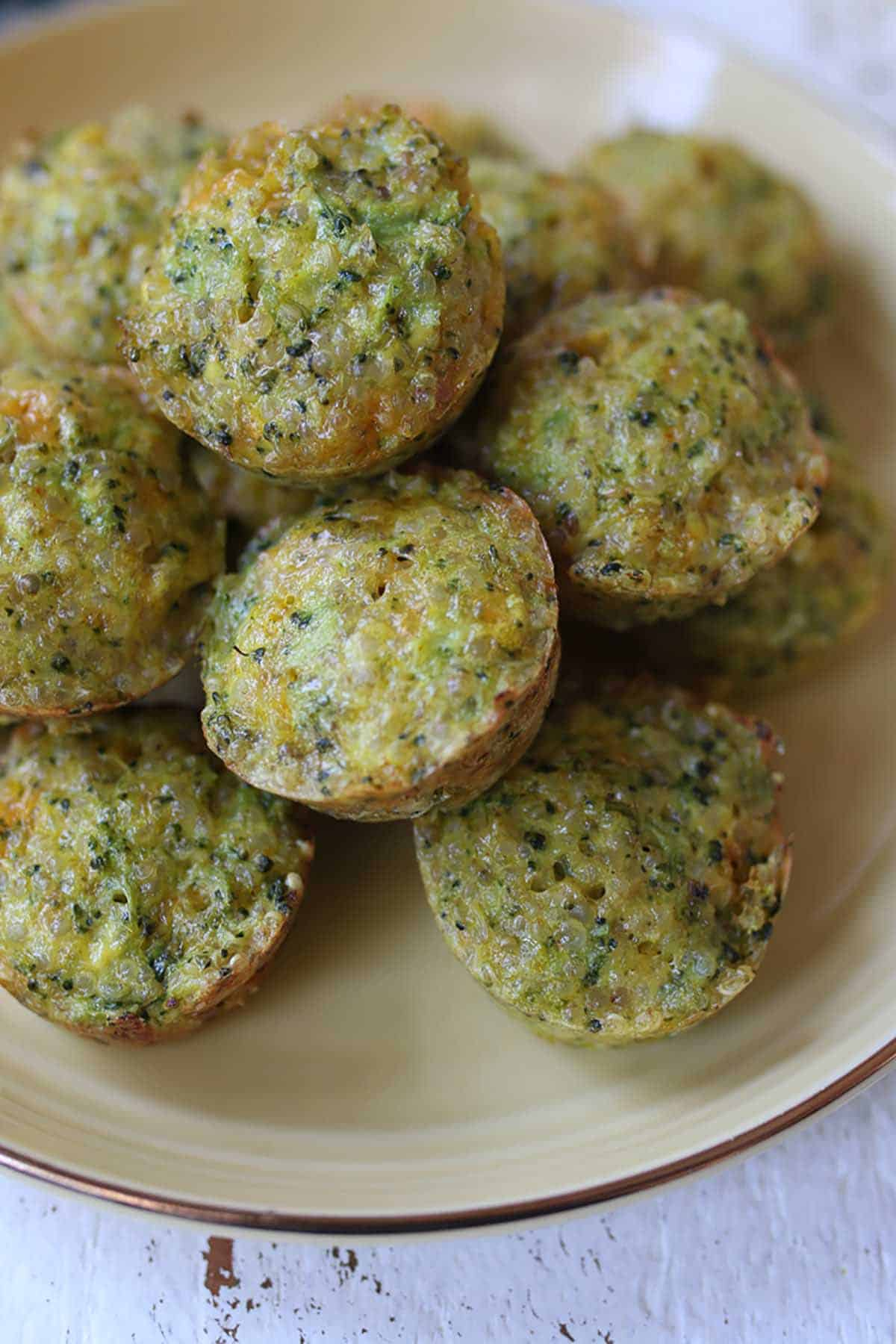 Several mini broccoli and cheese egg muffins on a yellow plate.