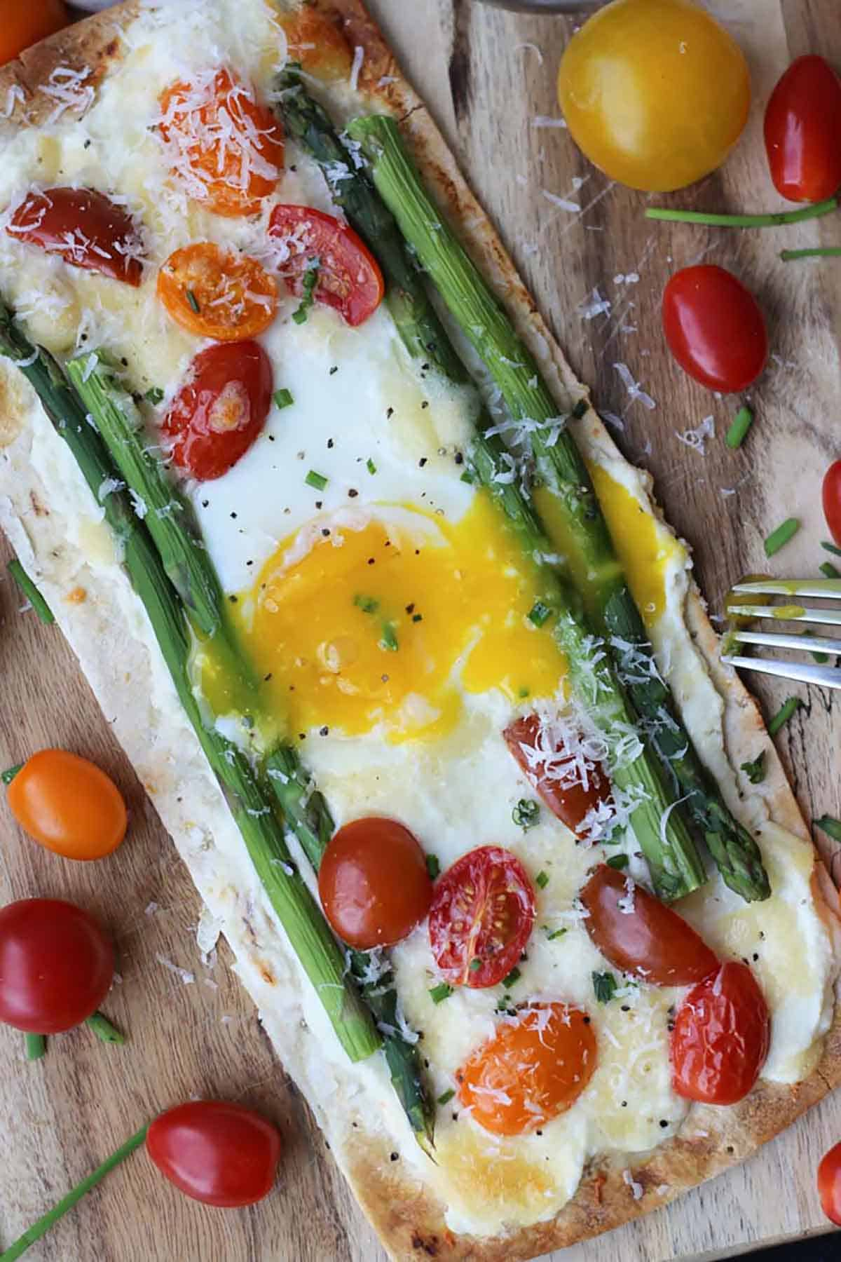 A vegetable pizza with an egg on top, asparagus, cherry tomatoes, and parmesan.