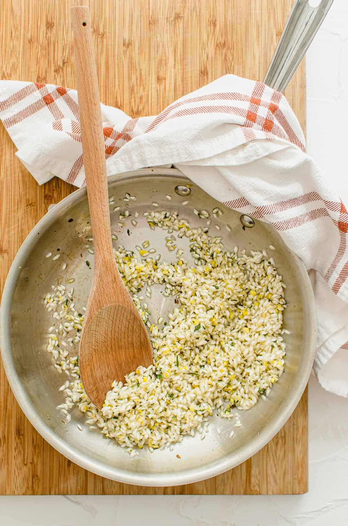 Dry arborio rice heating up in a pan with rosemary and sage.