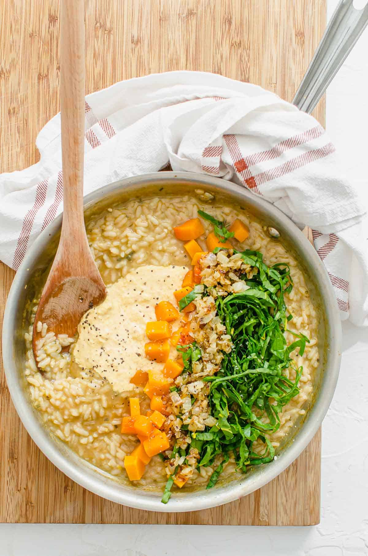 Cashew cream, butternut squash, swiss chard, and onions adding to risotto.