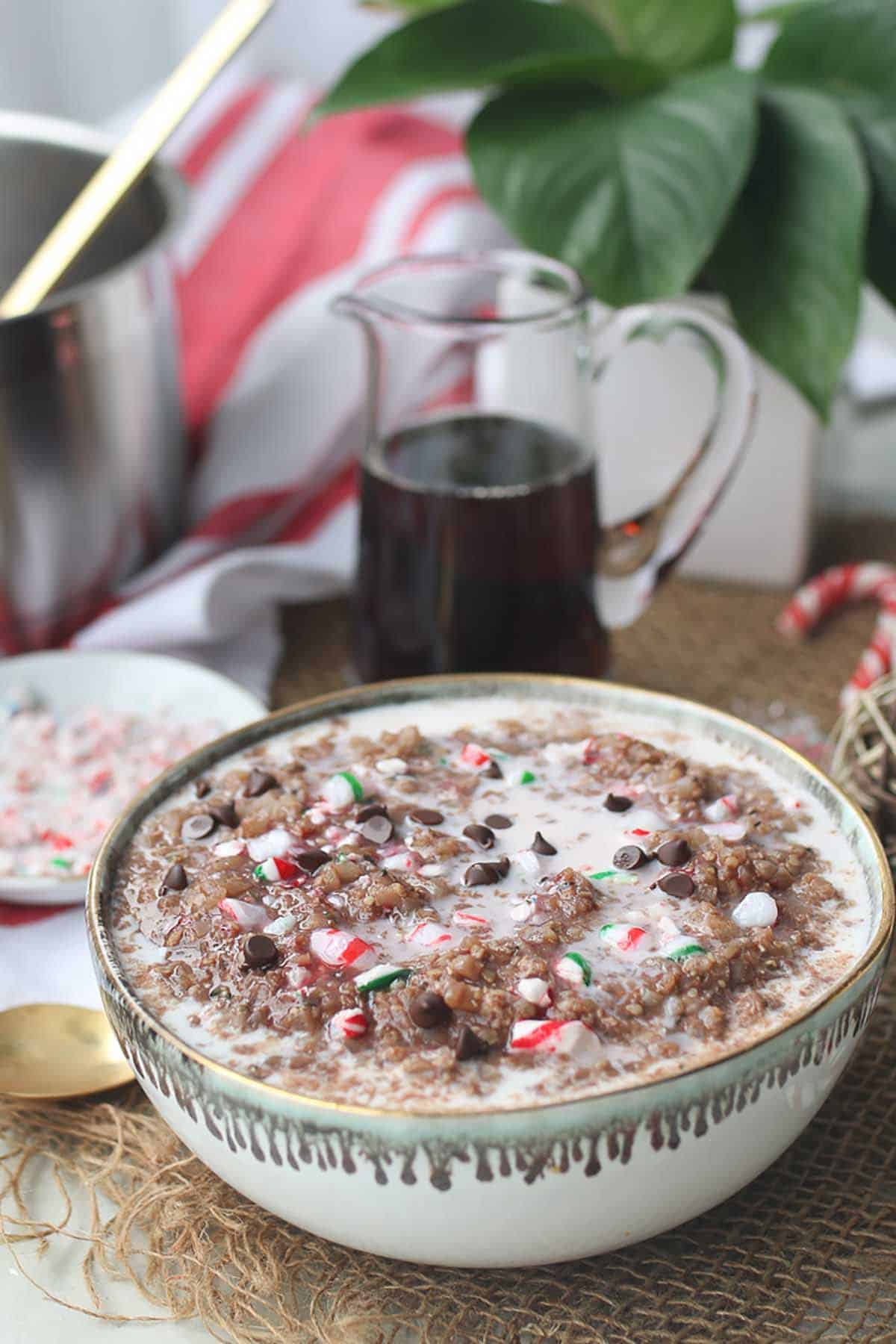 Christmas porridge in a white bowl topped with chocolate chips and candy canes.