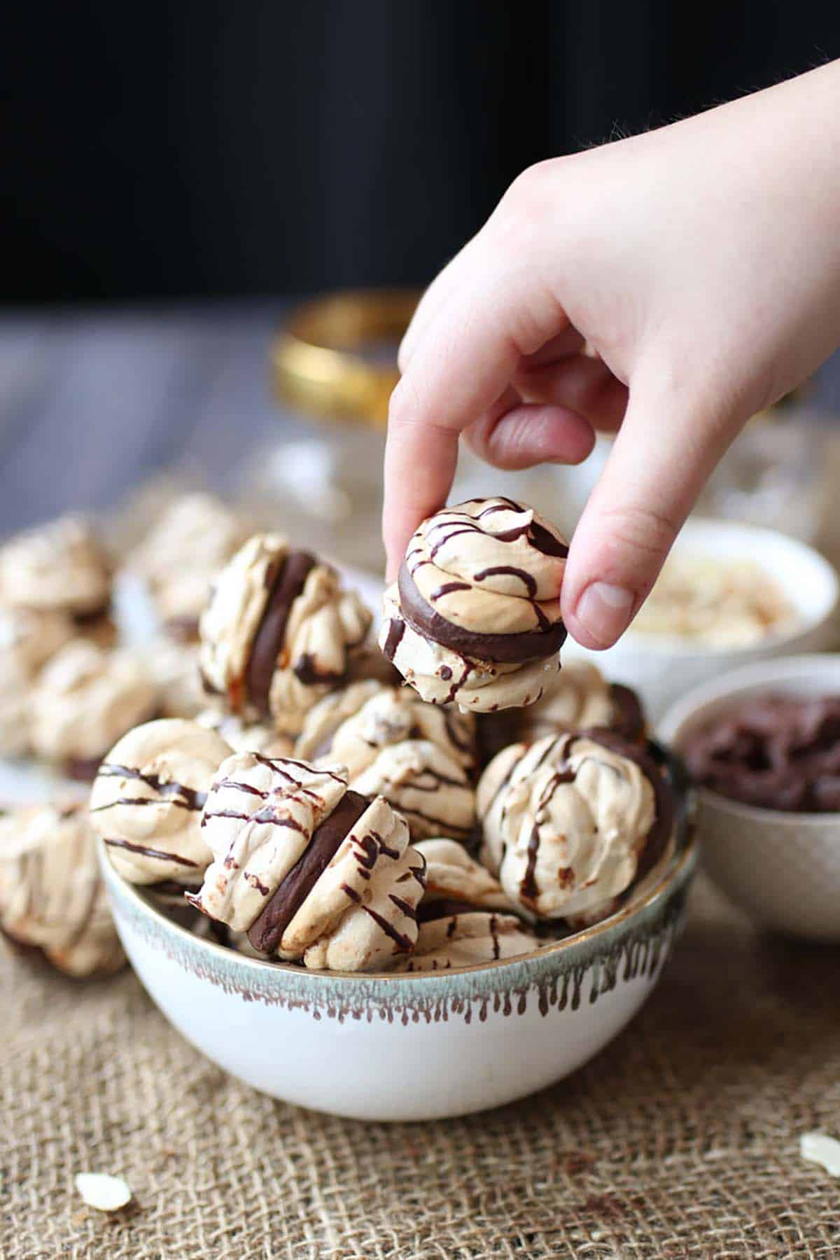A hand picking up a chocolate meringue cookie from a bowl.