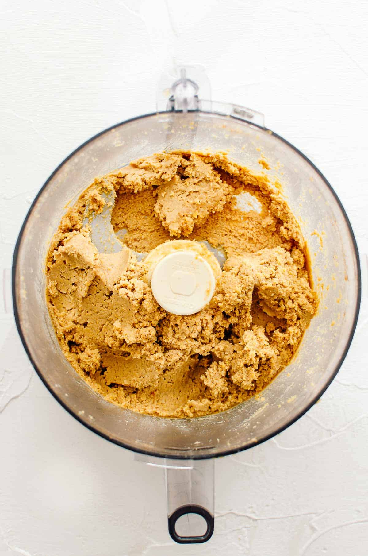 Birds eye view of chickpea cookie dough ingredients after having been mixed together in a food processor.