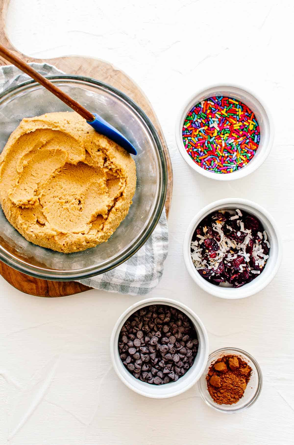 Chickpea cookie dough in a bowl with several add ins portioned on the side including chocolate chips, cocoa powder, cranberries and coconut, and sprinkles.