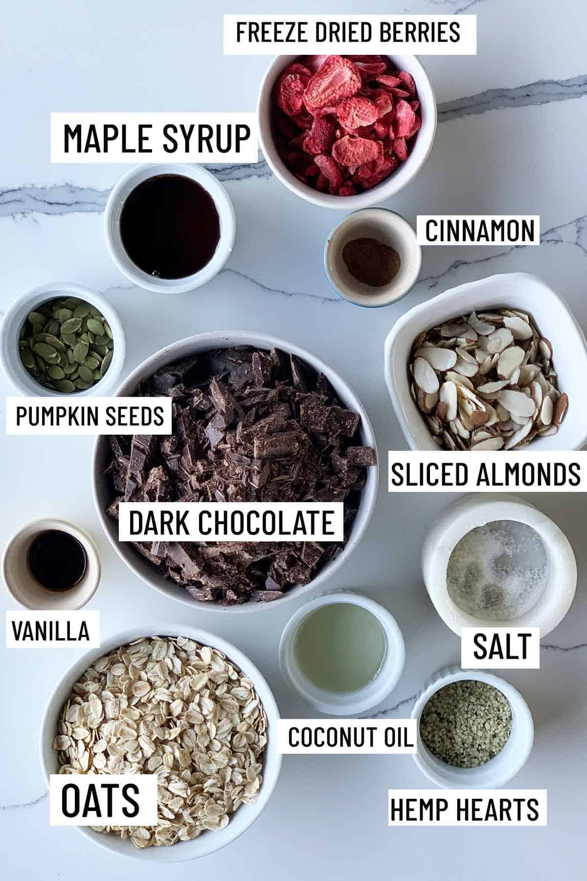 Birds eye view of portioned recipe ingredients for almond chocolate bark including freeze dried berries, maple syrup, cinnamon, pumpkin seeds, sliced almonds, dark chocolate, salt, vanilla, oats, coconut oil, and hemp hearts.