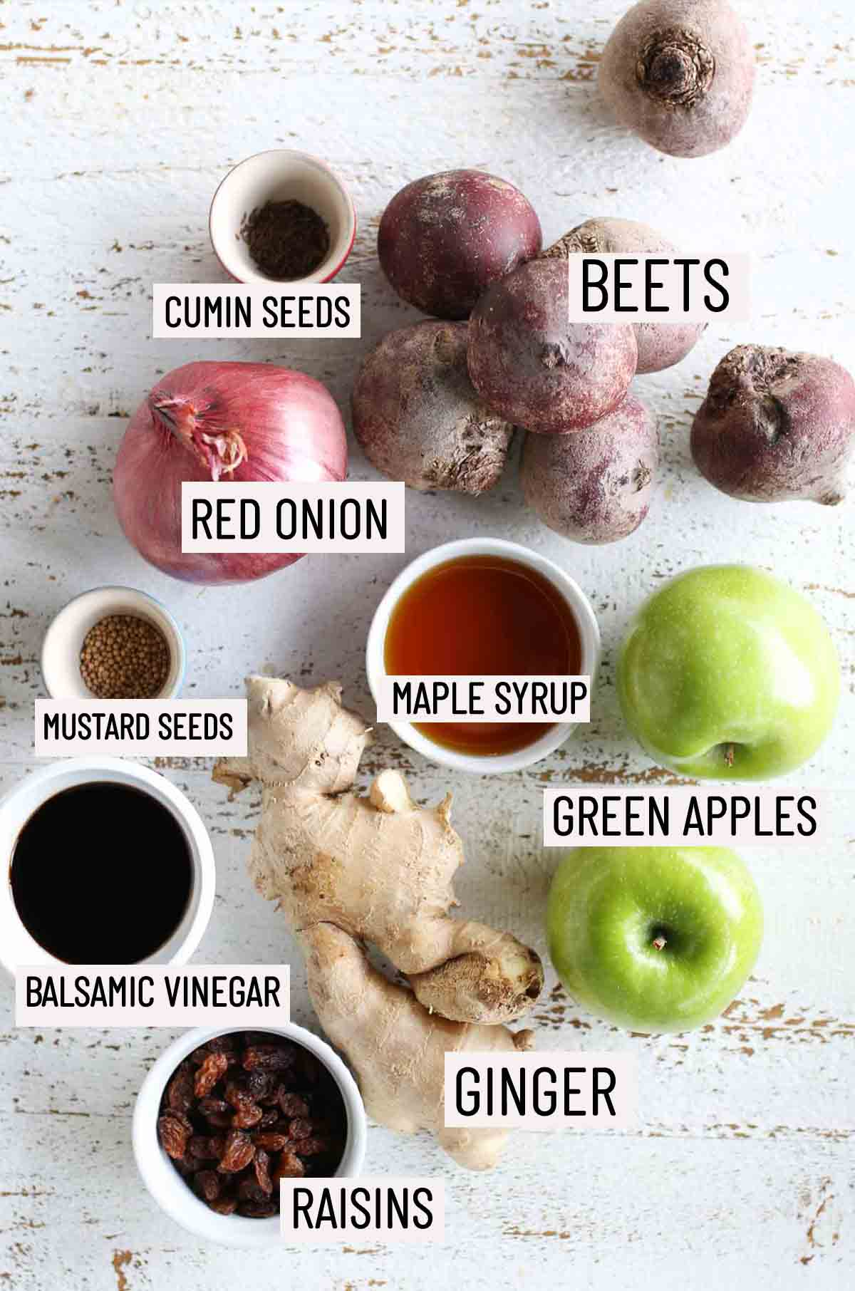 Birds eye view of portioned ingredients needed to make apple chutney including beets, red onion, cumin seeds, mustard seeds, maple syrup, green apples, ginger, balsamic vinegar, and raisins.