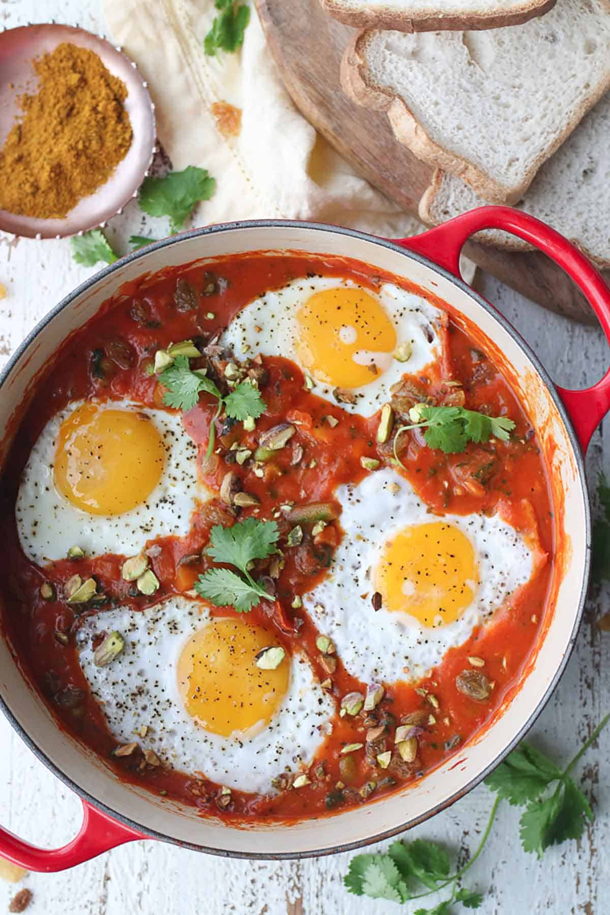 Birds eye view of a curry shakshuka in a sauce pan.