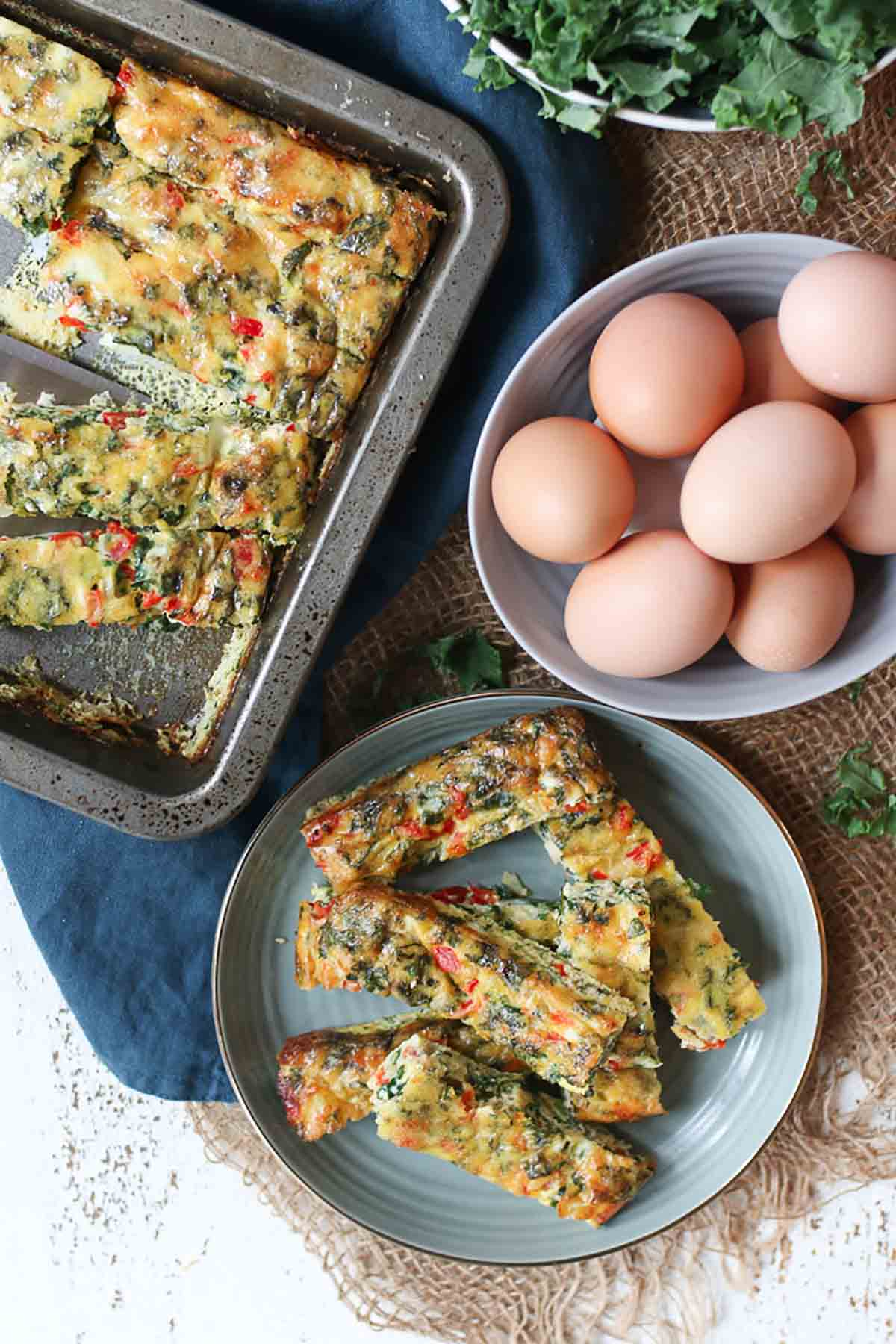 Birds eye view of a frittata cut up into slices on a plate, whole eggs in a bowl, and the remaining frittata on a baking tray.