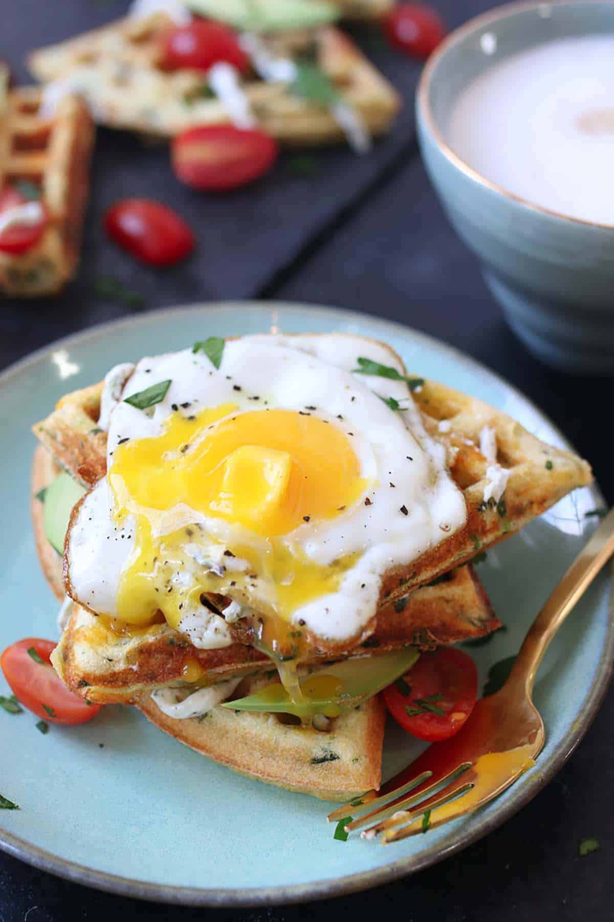 A fried egg on top of three waffles.