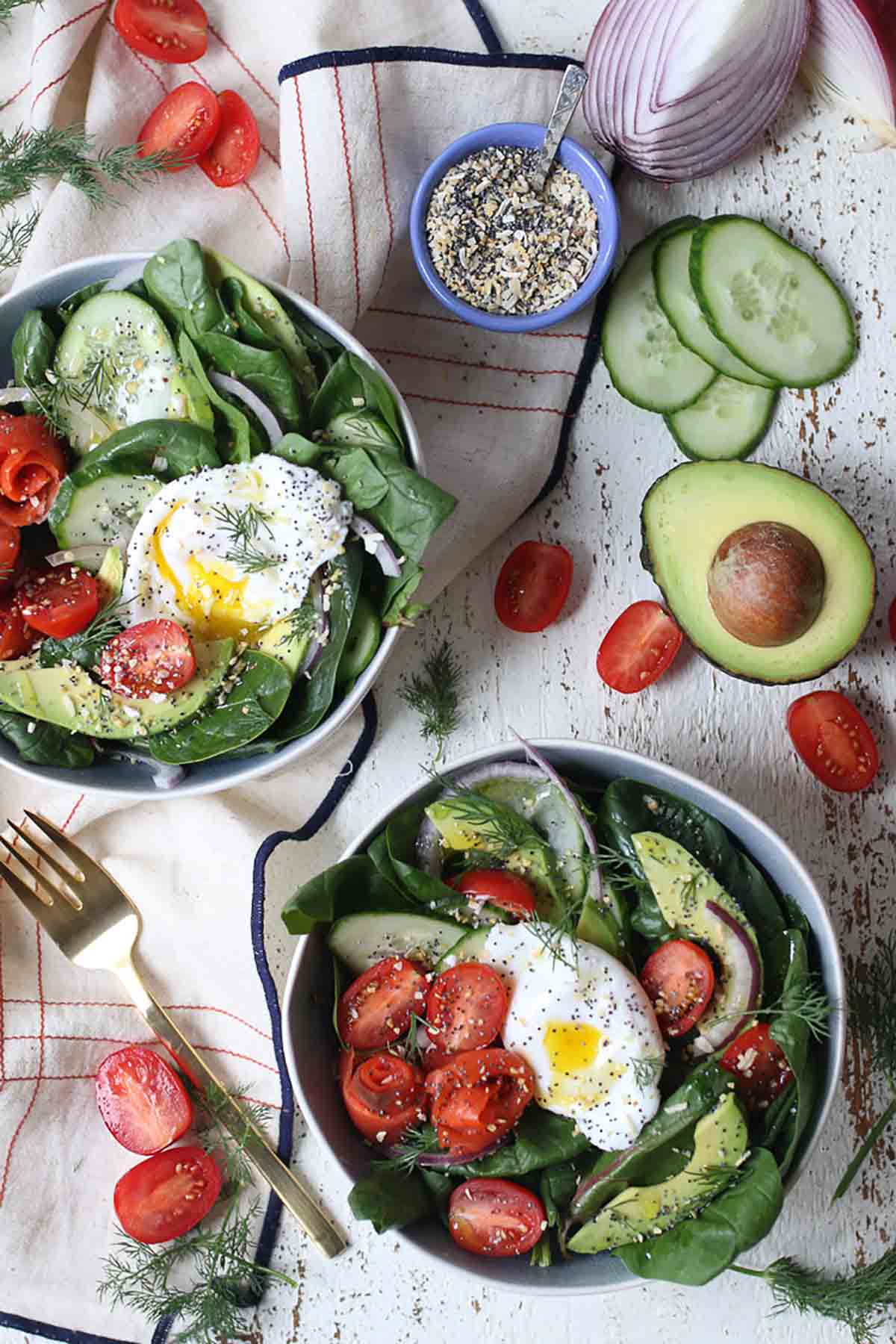 Birds eye view of two bowls of salad with a poached egg on top.