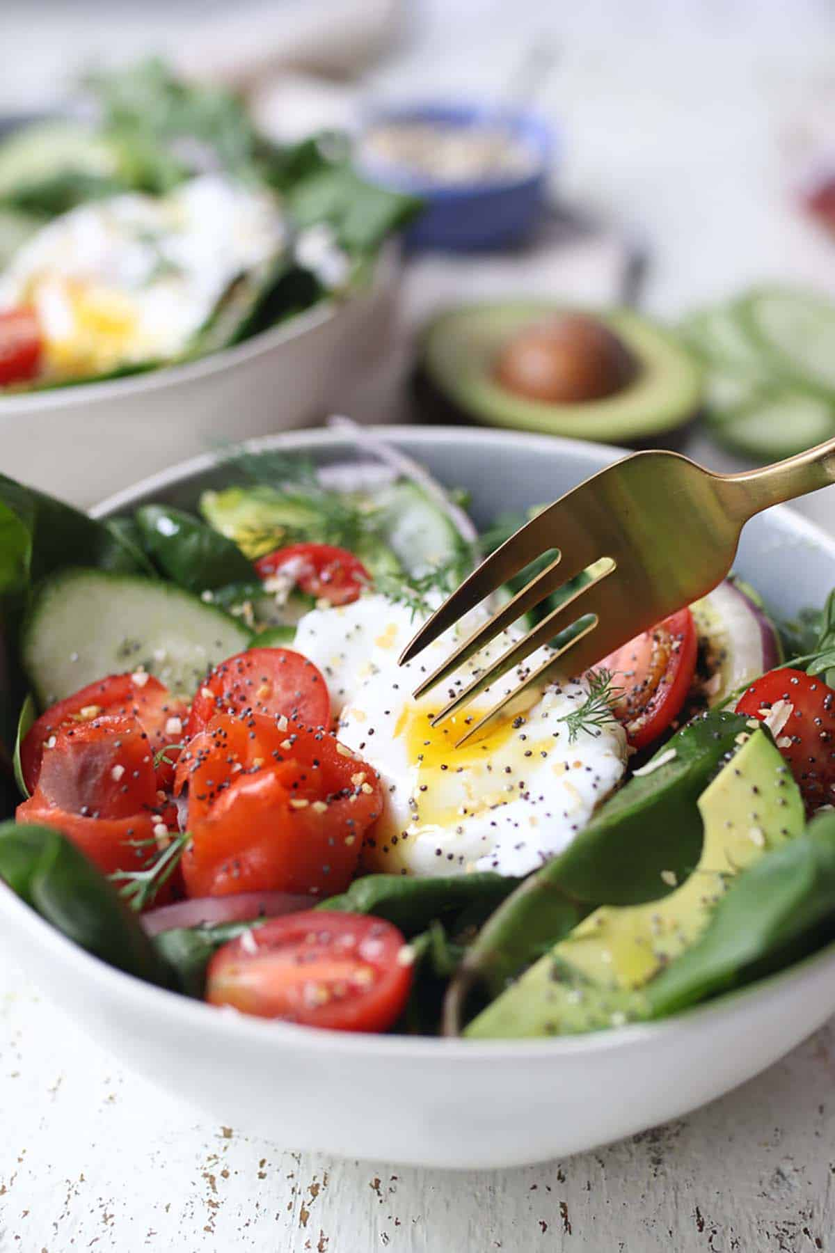 A fork cutting into a poached egg on a salad.