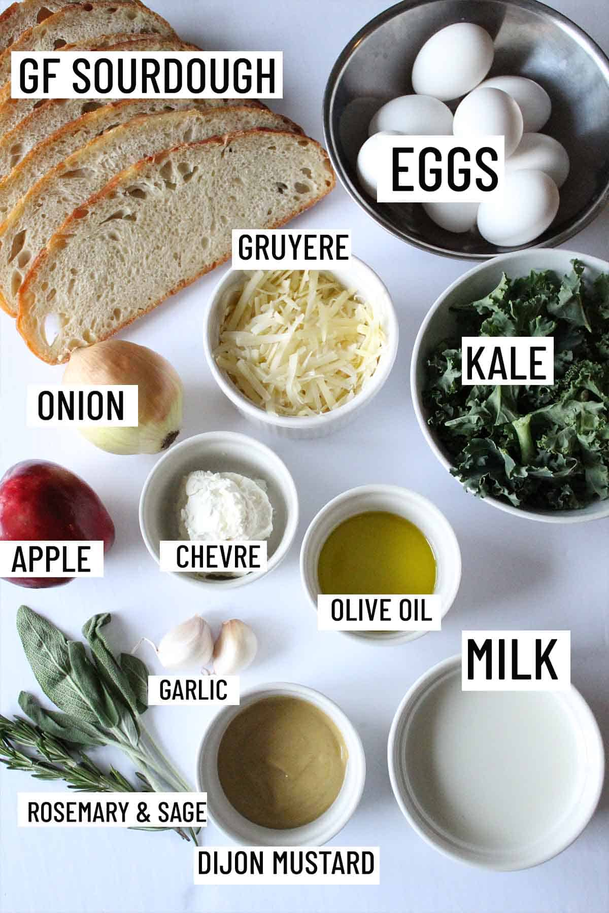 Birds eye view of strata ingredients including eggs, bread, kale, garlic, herbs, mustard, olive oil, onion, apple, and cheese.