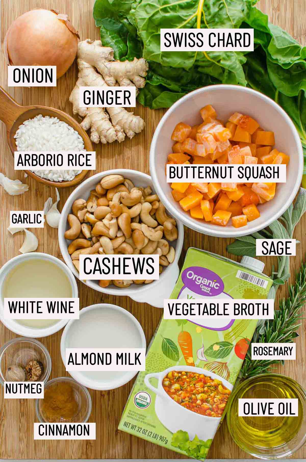 Portioned ingredients needs to make risotto including butternut squash, rice, wine, cashews, onion, garlic, swiss chard, sage, rosemary, broth, almond milk, olive oil, cinnamon, and nutmeg.
