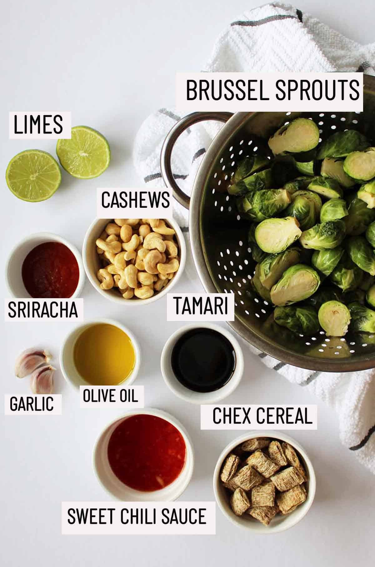 Birds eye view of portioned ingredients to make sweet and spicy brussel sprouts including brussel sprouts, lime, cashews, sriracha, garlic, olive oil, tamari, sweet chili sauce and chex cereal.
