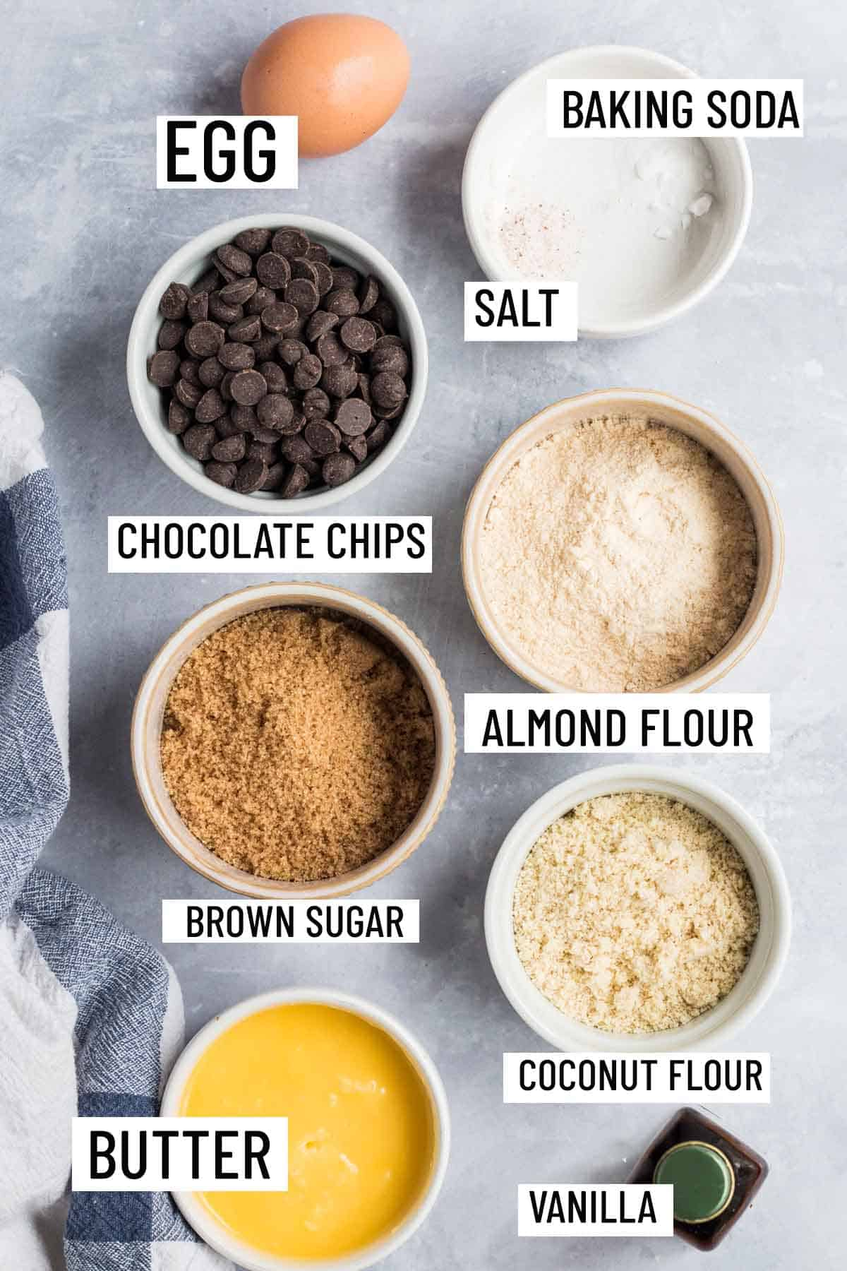Birds eye view of portioned ingredients to make coconut flour cookies including flour, butter, vanilla, brown sugar, chocolate chips, salt, baking soda, and an egg.