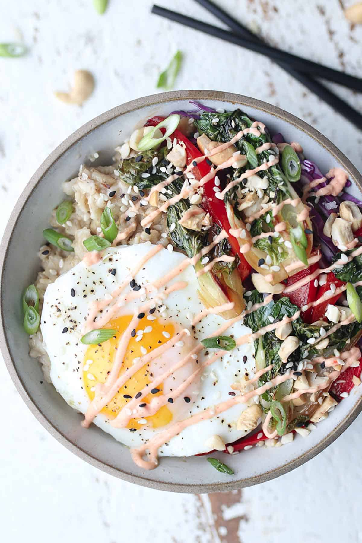 Birds eye view of a korean oatmeal bowl with an egg on top and sauteed veggies on the side and dirzzled with sauce.