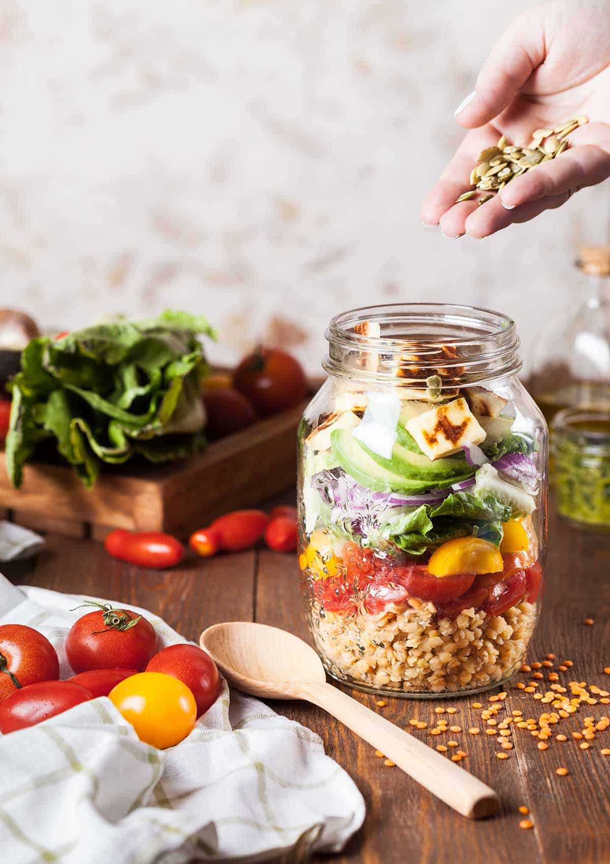 Several salad ingredients in a jar with a hand sprinkling some seeds on top.