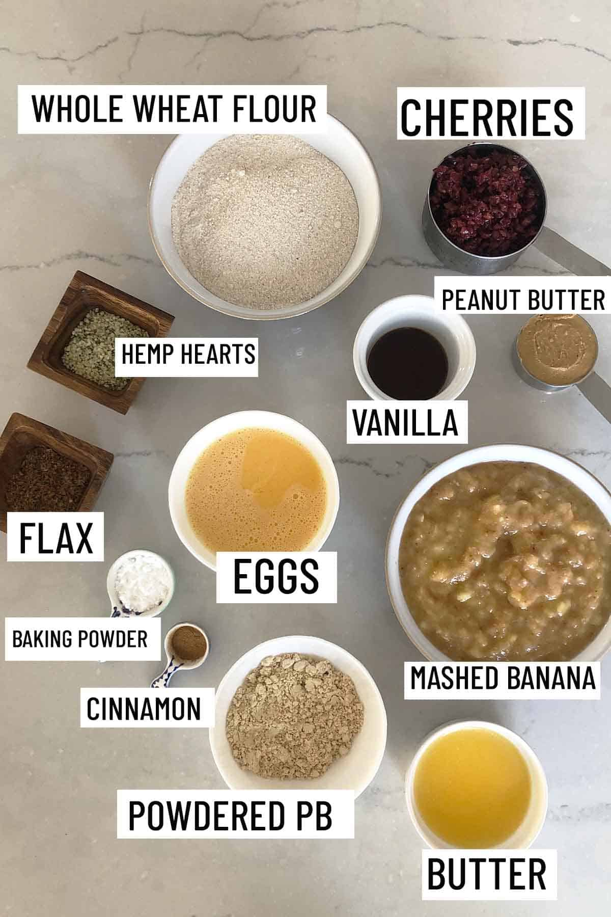 Birds eye view of portioned ingredients for recipes including butter, peanut butter, banana, cinnamon, baking powder, eggs, flax, hemp hearts, vanilla, cherries, and whole wheat flour.