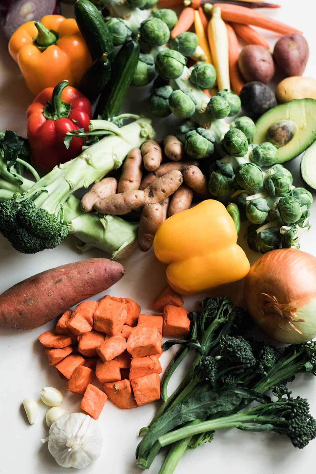 A large spread of colourful vegetables from a vegan grocery list including sweet potato, bell peppers, onion, broccoli, brussel sprouts, carrots, avocado, and zucchini.